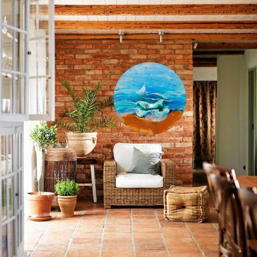 Round Abstract ocean with boat artwork hanging on wall above a chair in living-room