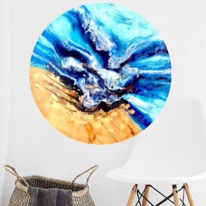 Round abstract beach artwork hanging on wall behind chair and basket