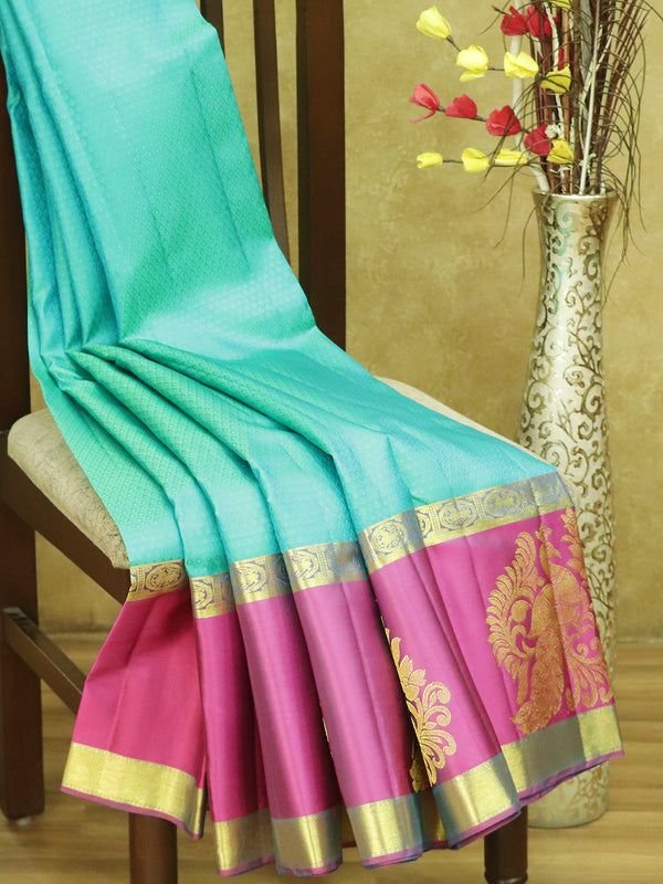 Pure kanjivaram silk saree dual shade of teal blue and magenta with allover self emboss and golden zari peacock butta border