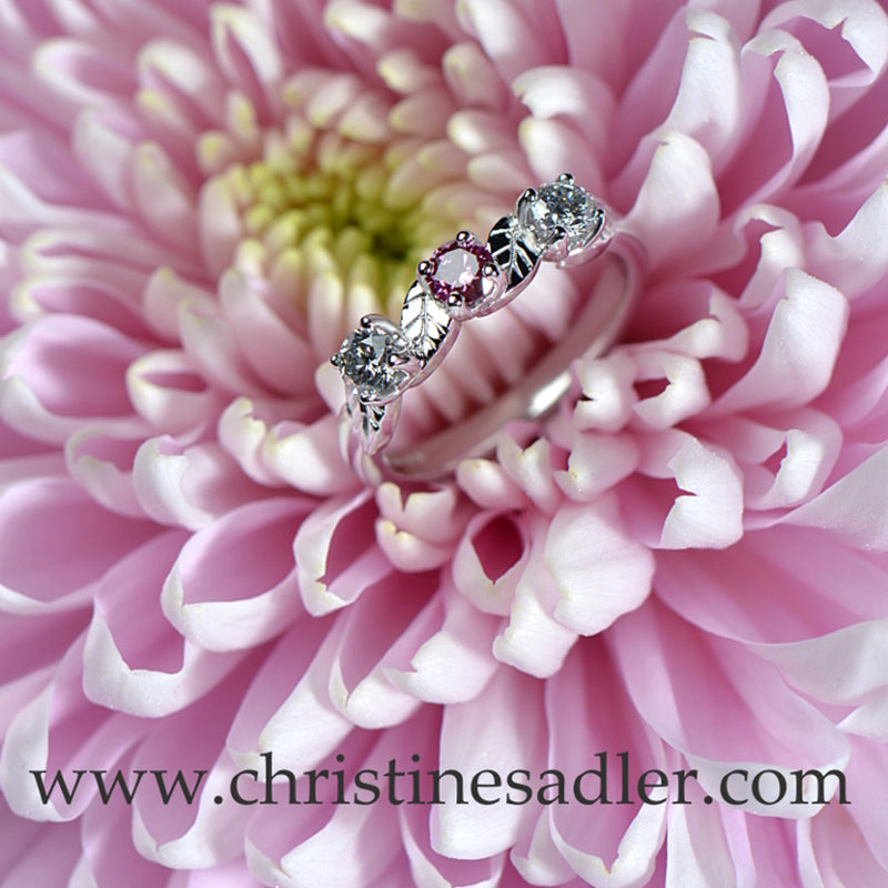 Pink diamond ring with two white diamonds in white gold