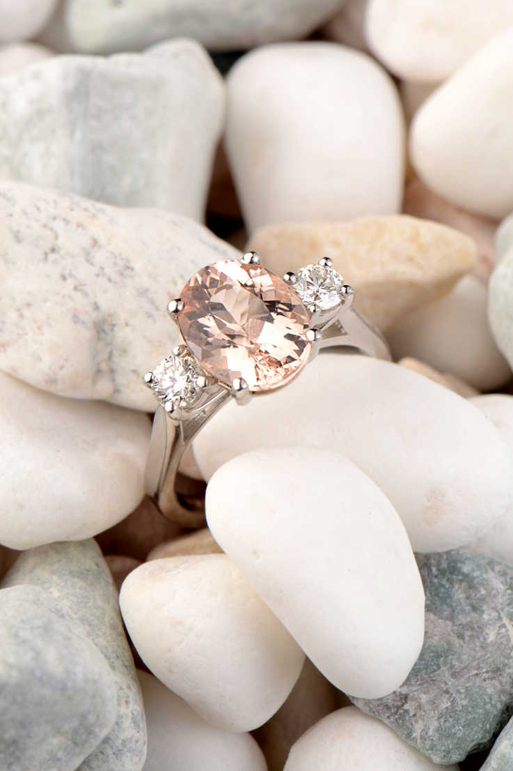 Oval cut morganite and diamond 18ct white gold ring on pebbles