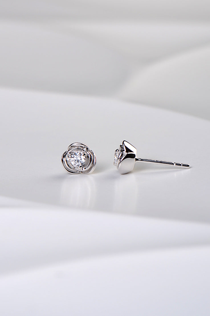 silver rose shaped earrings with overlapping petals and a clear cubic zirconia stone set in the middle