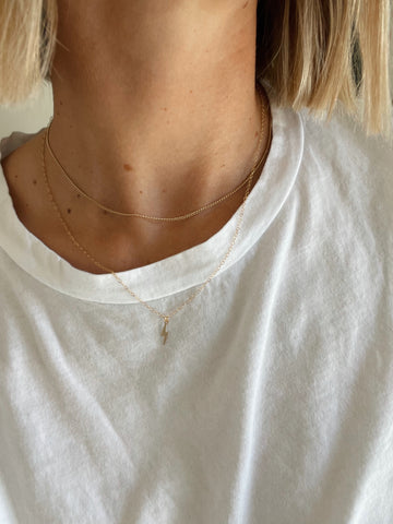 simple minimal gold layered jewelry on white tee