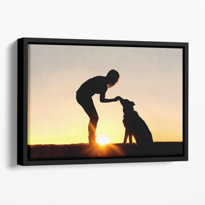 A silhouette of a girl sitting outside in the grass with her pet German Shepherd Mix Dog feeding him treats during training in front of a sunsetting sky. Floating Framed Canvas - Canvas Art Rocks - 1