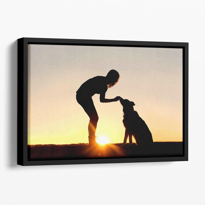 A silhouette of a girl sitting outside in the grass with her pet German Shepherd Mix Dog feeding him treats during training in front of a sunsetting sky. Floating Framed Canvas