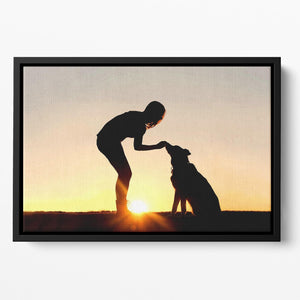 A silhouette of a girl sitting outside in the grass with her pet German Shepherd Mix Dog feeding him treats during training in front of a sunsetting sky. Floating Framed Canvas - Canvas Art Rocks - 2