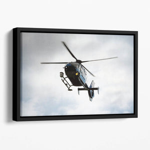 Blue and silver police helicopter flying above Floating Framed Canvas