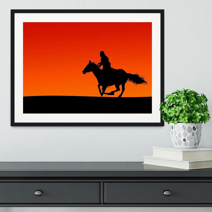 Silhouette of a horse and rider at sunset Framed Print