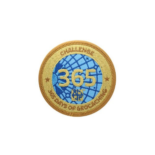 Patch with a gold background and blue centre that says 365 over the blue.  Around the edge says Challenge 365 Days of Geocaching.