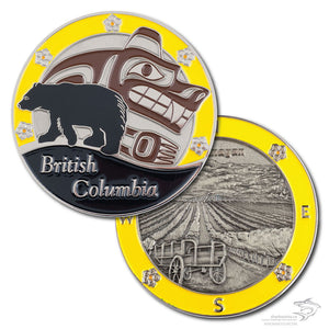 Both sides of the BC in Yellow coin are featured.  One shows a black bear over first nations art, with a yellow border and British Columbia written at the bottom.  The other side features the Okanagan Valley with a yellow border.