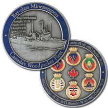 Picture of front and back of challenge coin.  It displays a ship on the front with a blue border, and 6 golden crests on the back, also surrounded by a blue border