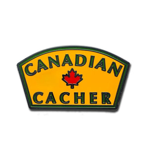 Canadian Cacher pin with yellow background and green writing with a red maple leaf in the centre