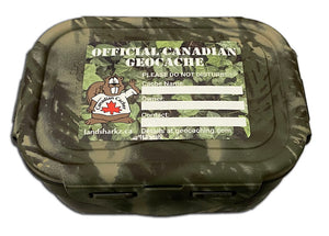 official canadian geocache sticker with ivy background, beaver dude on the right and areas to write the cache name, owner and contact details. Sticker is shown on a cache container with woodland camo paint.