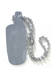 Back of trackable tag in matte aluminum showing detailed topography and compass rose details. A ball chain is attached.
