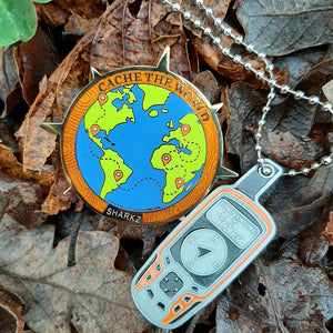 Polished gold geocaching coin and tag set feature a full colour globe with extended compass rose points, a GPS, geocaching gear, and detailed topography art.