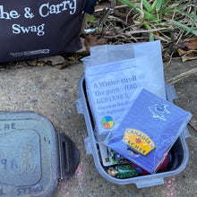 Yellow Canadian Cacher pin in a small cache with assorted trade items and a cache description