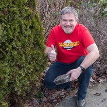 Man wearing a red Cachezinga T-Shirt holding a camo geocache doing a thumbs up