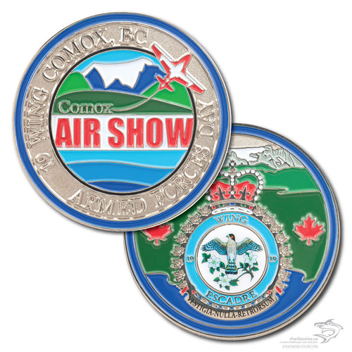 Comox Air Show coin, front and back, in polished silver with a Snowbird jet on the front, a crest with a printed bird on the back, with blues and greens and red writing