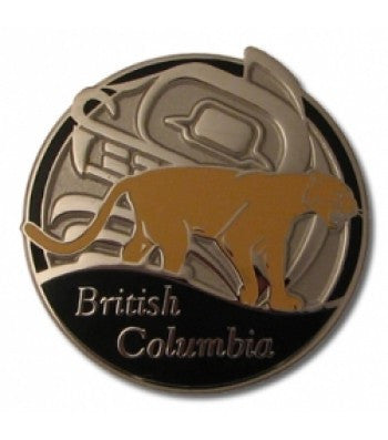 One inch diameter pin with a Haida design behind a brown cougar, with British Columbia written under him on black paint.