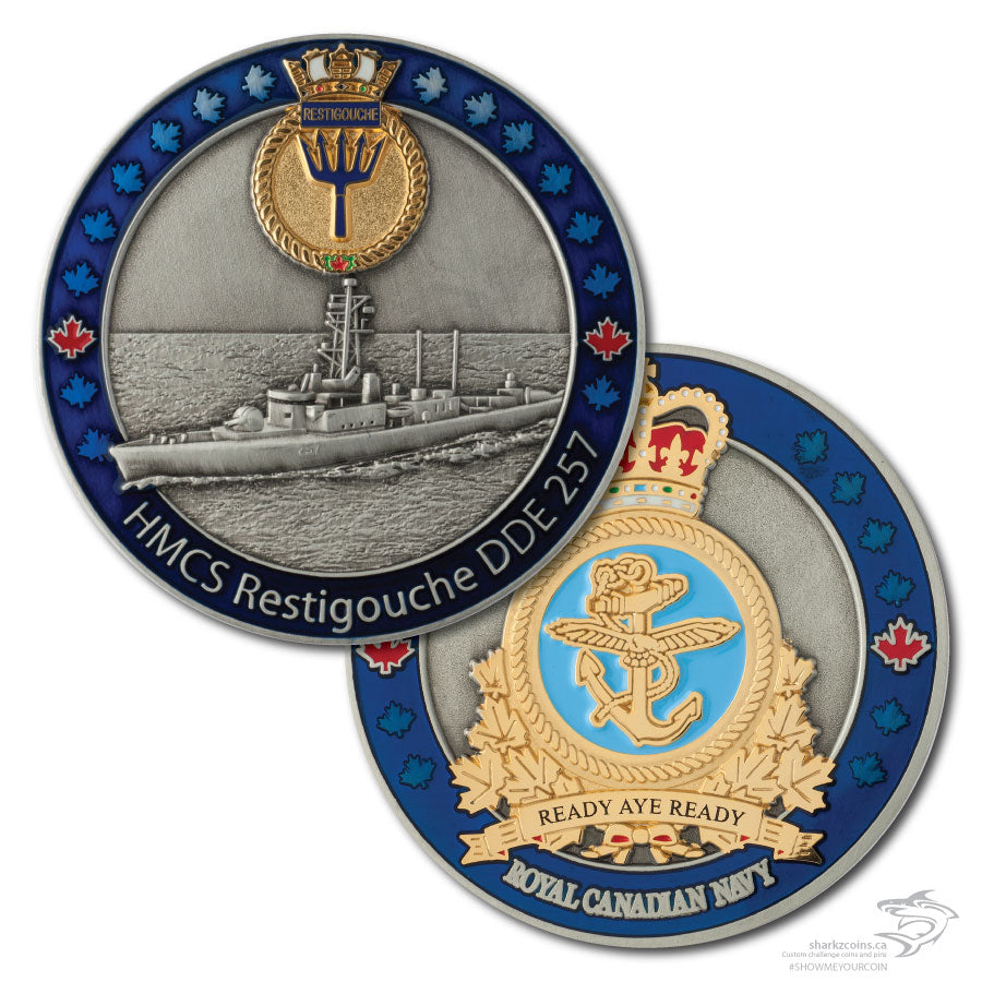 Both sides of the HMCS Restigouche.  The first is a 3D antique silver picture of the ship with a blue border and the ships crest at the top in polished gold.  The opposide side is the Royal Canadian Navy crest in polished gold with an antique silver background and the same blue border.