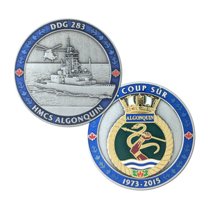Both sides of the HMCS Algonquin coin pictured.  Antique silver with a blue border, there is a 3D image of the ship and a helicopter on the front with the ships crest in polished gold on the back.