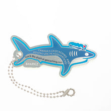 Opposite side of Landsharkz trackable tag.  A blue cartoon shark with the trackable code attached to a ball chain