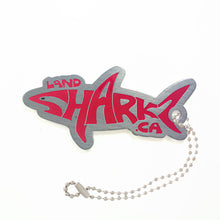 Shark shaped Landsharkz trackable tag that says Landsharkz in red, attached to a ball chain