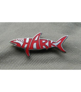 Shark shaped Landsharkz logo pin with red writing on a silver background