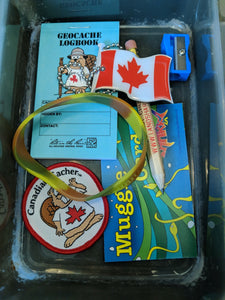 A geocache filled with various items, including a geocache logbook, bracelet, pencil, patch and the Canada Flag tag.