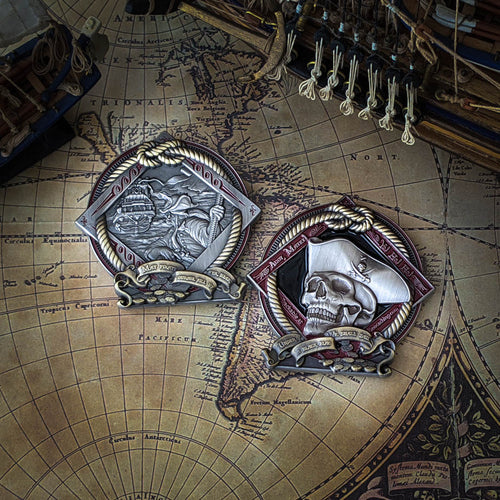 A two-tone antique silver and antique bronze pirate geocoin against a pirate map