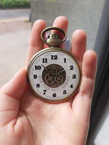 The front of the Retirement Pocket Watch Coin in someone's hand