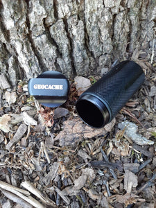 Close up of the black geocache with the lid off