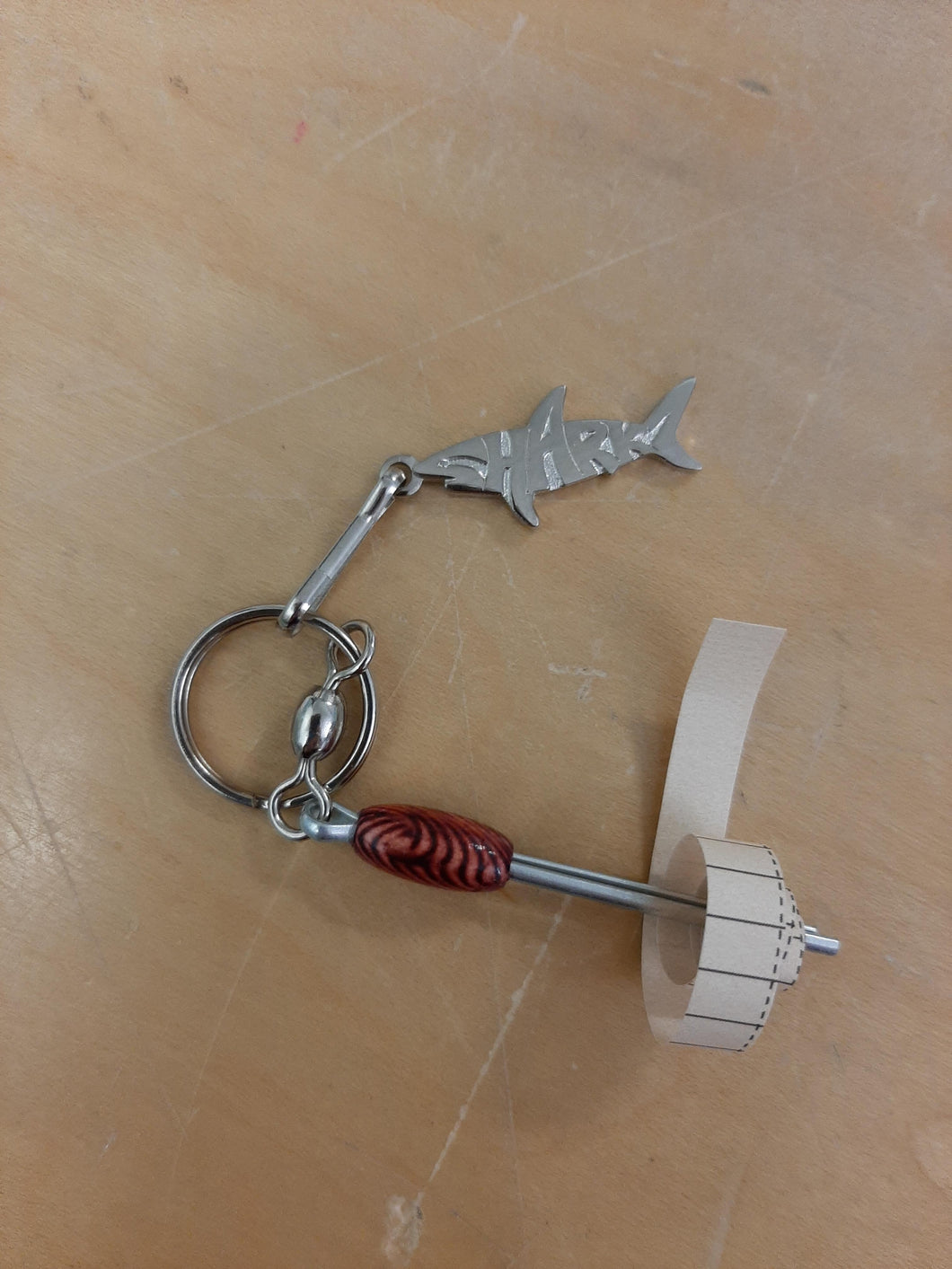 Silver Sharkz logo on a keychain with a nano log roller with a red bead