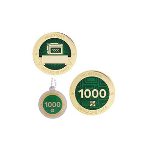 Milestone geocoin in gold with dark green paint for your 1000th find.  Front and back pictured, as well as the matching tag.