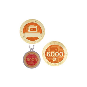 Milestone geocoin in gold with peach paint for your 6000th find.  Front and back pictured, as well as the matching tag.