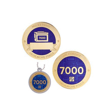 Milestone geocoin in gold with indigo paint for your 7000th find.  Front and back pictured, as well as the matching tag.