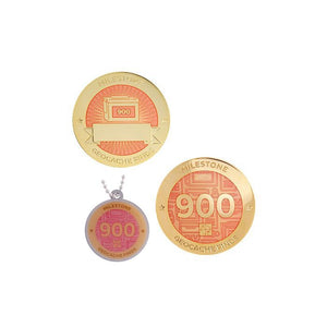 Milestone geocoin in gold with peach paint for your 900th find.  Front and back pictured, as well as the matching tag.
