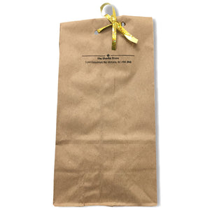 "Brown paper bag with ""The Sharkz Store"" written on it, tied closed with a gold ribbon."