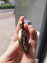 A side view of the Retirement Pocket Watch coin in someone's hand