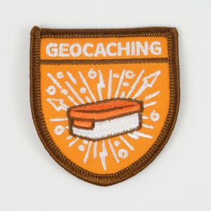 "Shield shaped orange patch with a brown border.  It says ""Geocaching"" at the top and has a picture of a geocache under it."