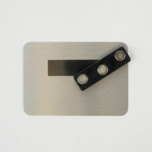 The back of a single tag.  It is metal with a a magnet that would hold it to your shirt.