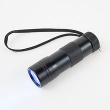 Black Ultra Violet LED Flashlight with cord switched on