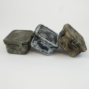 Small Camouflaged containers in woodland, stone and khaki