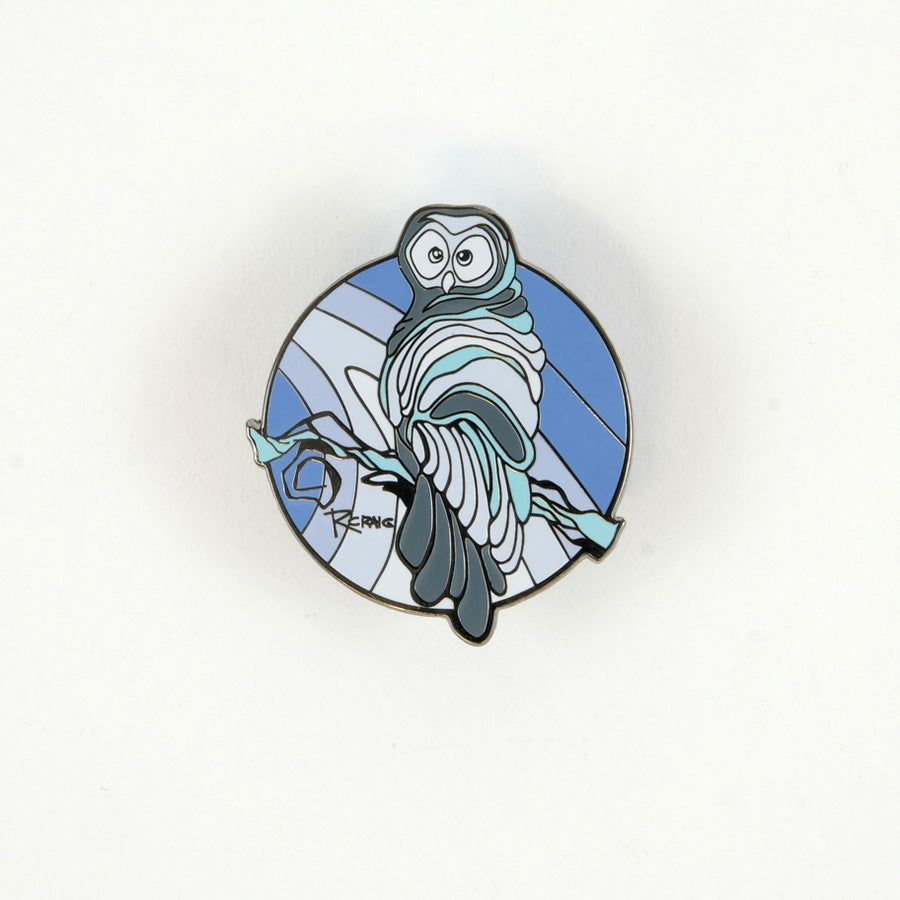 Circular pin with an owl and different bands of different colours of blue and grey