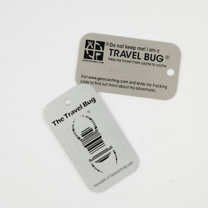 Travel Bug tag, both sides pictured.  There is space on the back for a tracking number with the signature beetle on the front.