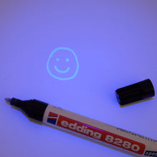 Edding 8280 UV Marker with UV light shining on it and a glowing happy face, drawn by the marker