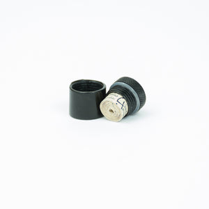 The black magnetic nano cache with a rolled up log sheet in it.
