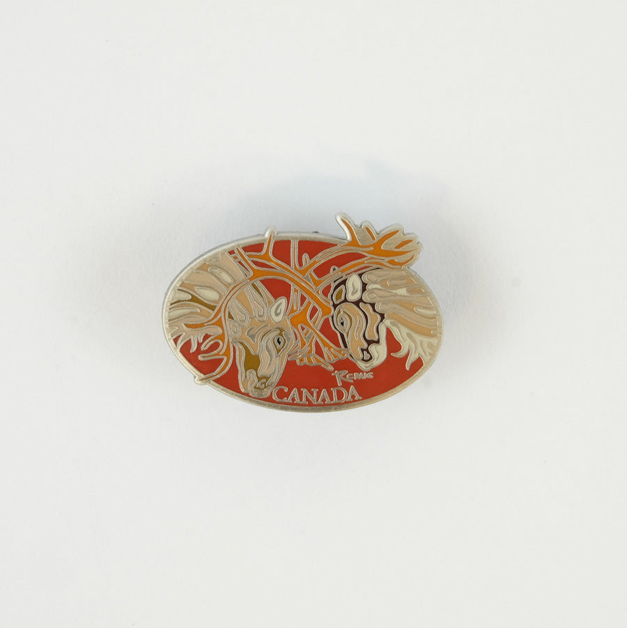 Small red pin, a horizontal oval with 2 caribou clashing their antlers together.  It says Canada at the bottom.
