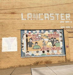 "picture of brick wall with the word ""Lancaster"" and a mural celebrating diversity and Lancaster city"