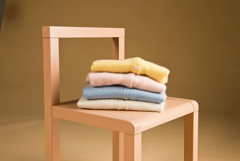Oscar and Me cashmere cardigans stacked on a Ferm Living chair